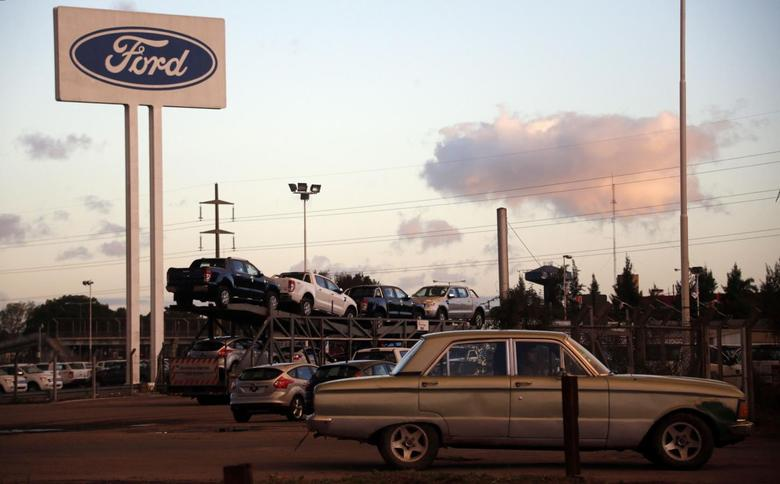 An old Ford Falcon drives by the entrance of the parking lot of the Ford factory in Pacheco, on the outskirts of Buenos Aires, May 22, 2014.  REUTERS/Marcos Brindicci