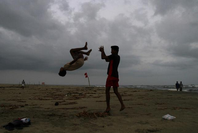 Boys practice somersaulting on a beach against the backdrop of pre-monsoon clouds in the southern Indian city of Kochi June 3, 2014.  REUTERS/Sivaram V