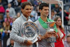 Second-placed Rafael Nadal (L) of Spain and first-placed Novak Djokovic of Serbia pose with their trophies after the men's singles final match at the Rome Masters tennis tournament May 18, 2014. REUTERS/Giampiero Sposito