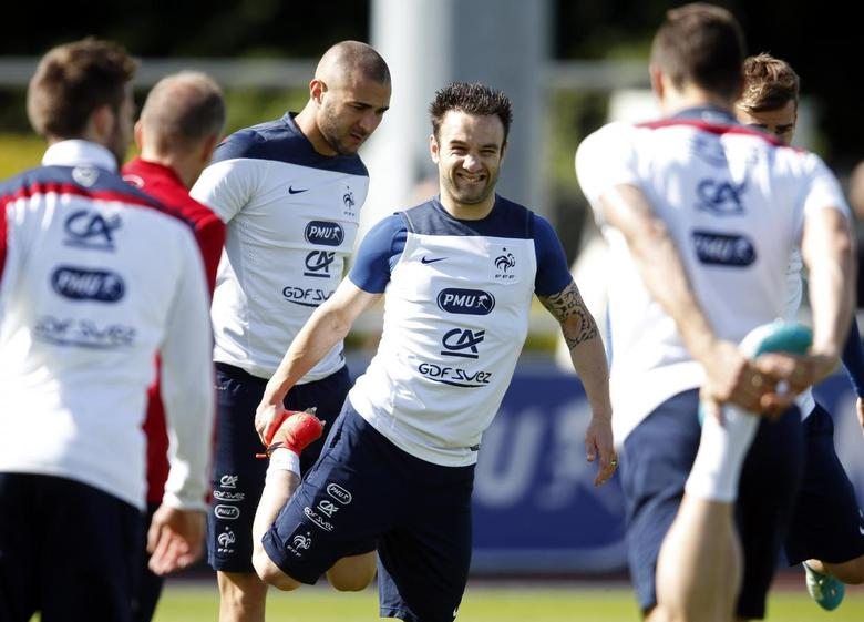 France's national soccer team players Mathieu Valbuena (C) and Karim Benzema stretch during a training session in Clairefontaine, near Paris, in preparation for the upcoming 2014 World Cup, June 4, 2014.   REUTERS/Charles Platiau