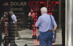 Мужчина у обменного пункта в Буэнос-Айресе 31 января 2014 года. Курс евро стабилизировался после значительного роста с четырехмесячного минимума в четверг, когда Европейский центральный банк в соответствии с прогнозами принял ряд мер для предотвращения дефляции в еврозоне. REUTERS/Stringer