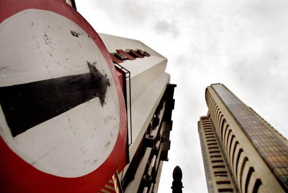 A road sign stands next to the Bombay Stock Exchange building (R), August 3, 2005. REUTERS/Arko Datta/Files