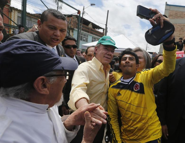 Colombia's President and presidential candidate Juan Manuel Santos (C) greets and takes a photo with supporters during a campaign rally in Bogota June 5, 2014.  REUTERS/John Vizcaino
