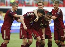 Игроки сборной России радуются голу, забитому в ворота команды Алжира в товарищеском матче в Москве 6 июня 2014 года. Сборная России по футболу обыграла команду Марокко со счетом 2-0 в товарищеском матче в рамках подготовки к чемпионату мира, на следующей неделе стартующему в Бразилии. REUTERS/Grigory Dukor
