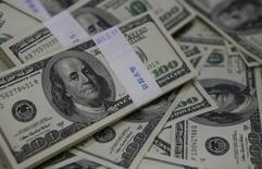 Imagen de archivo de pilas de billetes de 100 dólares en un banco en Seúl, ago 2 2013. Los inversores recortaban sus tenencias en dólares el viernes tras la publicación de un sólido reporte laboral en Estados Unidos que dejó pocas probabilidades de que la Reserva Federal se aparte del objetivo de poner fin gradualmente a sus medidas de estímulo monetario en ese país. REUTERS/Kim Hong-Ji