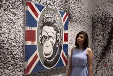"""El reservado artista callejero británico Banksy suele pintar fachadas por la noche y se ha quejado cuando han retirado sus obras para revenderlas, por lo que seguramente le enfurecerá que Sotheby's ofrezca unas 70 piezas en una """"venta privada"""" en Londres. En la imagen una asitente de la galeria de arte londinense observa observa la obra """"Monkey Queen"""" de Banksy en Londres el 6 de junio de 2014.   REUTERS/Neil Hall"""