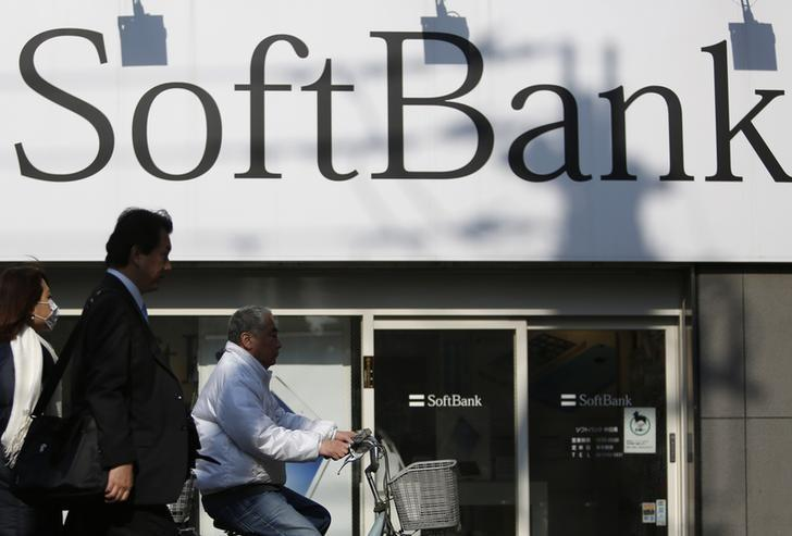 Pedestrians walk in front of a SoftBank Corp logo outside its branch in Tokyo February 25, 2014. REUTERS/Yuya Shino/Files