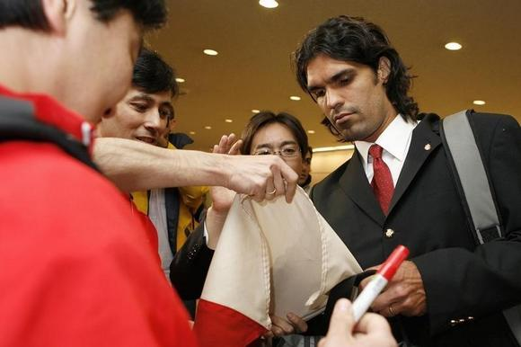Fernandao signs an autograph for fans at Narita International Airport near Tokyo December 7, 2006. REUTERS/Kiyoshi Ota/Files