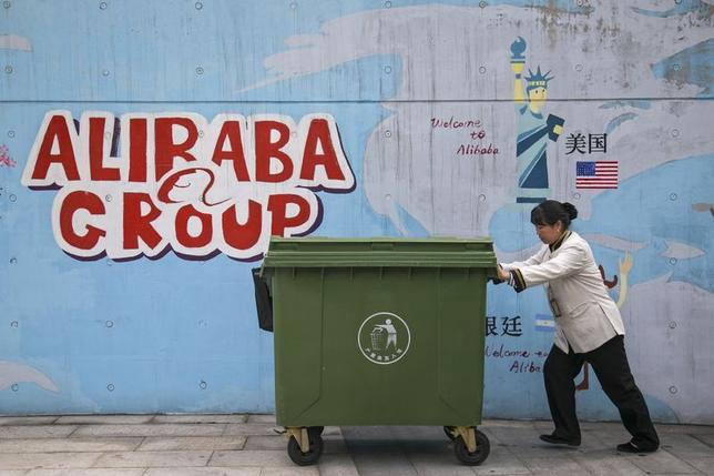 A worker pushes a trash container past a wall with graffiti at Alibaba's headquarters on the outskirts of Hangzhou, Zhejiang province April 23, 2014. REUTERS/Chance Chan/Files