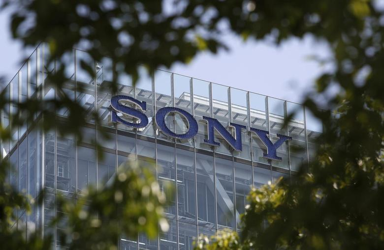 A logo of Sony Corp atop the company headquarters is seen through leaves in Tokyo May 22, 2014. REUTERS/Yuya Shino/Files