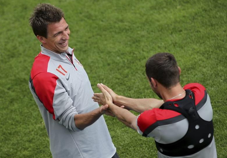 Croatia's national soccer team player Mario Mandzukic (L) smiles during a training session in Bad Tatzmannsdorf May 25, 2014. REUTERS/Antonio Bronic/Files