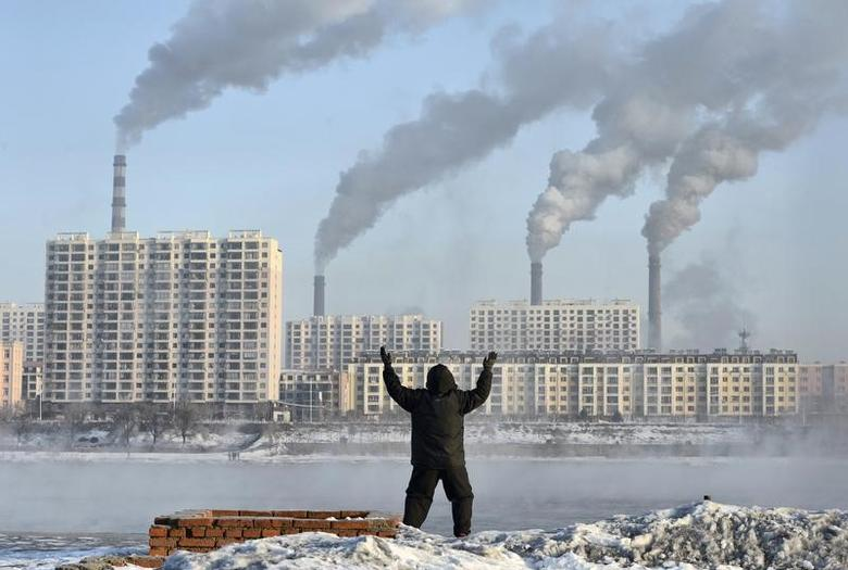 An elderly man exercises in the morning as he faces chimneys emitting smoke behind buildings across the Songhua river in Jilin, Jilin province, February 24, 2013.  REUTERS/Stringer