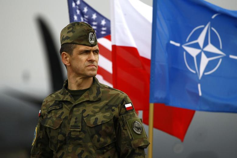 A Polish soldier stands near U.S. and Poland's national flags and a NATO flag as the first company-sized contingent of about 150 U.S. paratroopers from the U.S. Army's 173rd Infantry Brigade Combat Team based in Italy arrived to participate in training exercises with the Polish army in Swidwin, northern west Poland April 23, 2014. REUTERS/Kacper Pempel