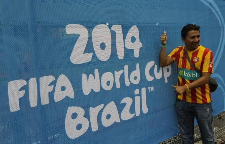 A soccer fan poses in front of a banner at the entrance to the Arena Baixada soccer stadium in Curitiba, June 9, 2014. The stadium will host the first of four 2014 World Cup matches on June 16. REUTERS/Henry Romero (BRAZIL  - Tags: SPORT SOCCER WORLD CUP)   - RTR3SWSE