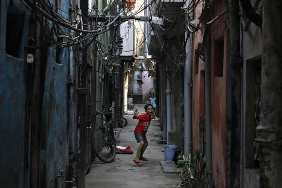 A boy reacts to the camera as he plays in an alley in New Delhi September 23, 2013. REUTERS/Adnan Abidi/Files