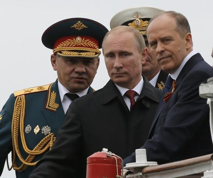 Russian President Vladimir Putin (C), Defence Minister Sergei Shoigu (L) and Russia's Federal Security Service (FSB) Director Alexander Bortnikov watch events to mark Victory Day in Sevastopol May 9, 2014.   REUTERS/Maxim Shemetov