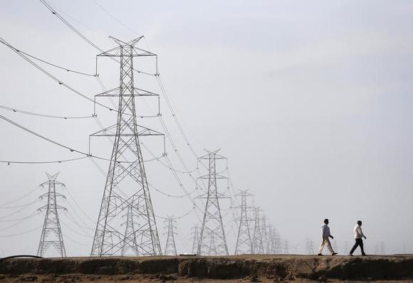 Men walk past electric pylons in Little Rann of Kutch in Gujarat March 2, 2014. REUTERS/Ahmad Masood/Files