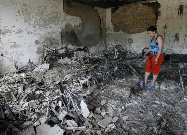 A woman stands near charred debris in a bicycle store after what locals say was overnight shelling by Ukrainian forces, in the eastern Ukrainian town of Slaviansk June 9, 2014.  REUTERS/Gleb Garanich