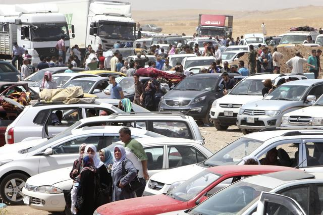 Families fleeing the violence in the Iraqi city of Mosul wait at a checkpoint in outskirts of Arbil, in Iraq's Kurdistan region, June 10, 2014.  REUTERS/Azad Lashkari