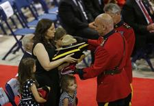 Nadine Larche, the widow of Royal Canadian Mounted Police officer Douglas James Larche, accepts her husband's hat and flag during a regimental funeral for three officers who were killed last week in Moncton, New Brunswick, June 10, 2014.     REUTERS/Mark Blinch