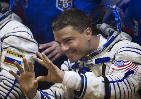 The International Space Station crew member Reid Wiseman of the U.S. waves to his family after donning a space suit at the Baikonur cosmodrome May 28, 2014.  REUTERS/Shamil Zhumatov