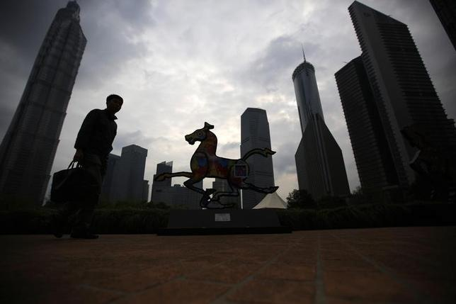 A man walks next to a horse statue in a park at Pudong financial district in Shanghai April 2, 2014. REUTERS/Carlos Barria/Files