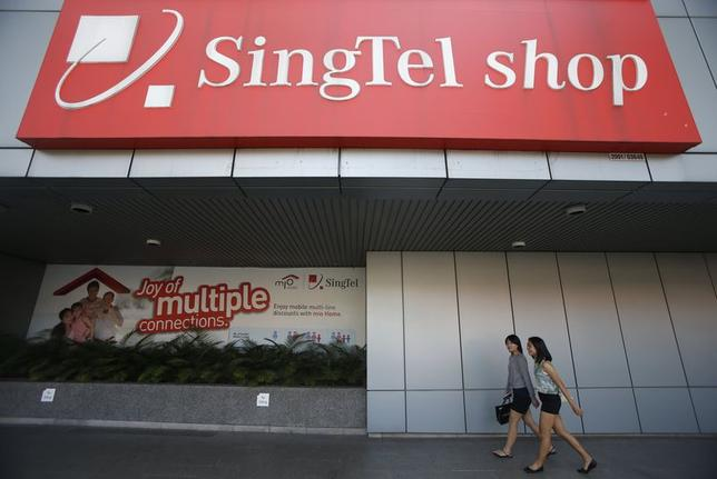 People pass a SingTel shop signage outside their head office in Singapore May 15, 2014.  REUTERS/Edgar Su