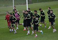 Игроки сборной Испании на тренировке в Куритибе 10 июня 2014 года. Испанцы способны варьировать свою традиционную модель игры, основанную на владении мячом, если их оппоненты по группе B выстроят плотную линию обороны, утверждает рулевой действующих чемпионов мира Висенте дель Боске. REUTERS/Henry Romero