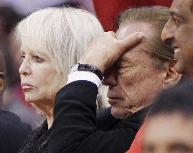 Los Angeles Clippers owner Donald Sterling (R) puts his hand over his face as he sits courtside with his wife Shelly (L) while the Clippers trail the Chicago Bulls in the second half of their NBA basketball game in Los Angeles in this December 30, 2011 file photo. REUTERS/Danny Moloshok/Files
