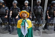 Garoto, envolto com a bandera do Brasil, se posiciona à frente de policiais durante a greve dos metroviários em São Paulo, a poucos dias da Copa do Mundo. Informações de que protestos se tornem violentos antes da partida de abertura do Mundial, nesta quinta-feira, preocupam a polícia. 09/06/2014 REUTERS/Damir Sagolj