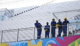 Operários da Arena Corinthians assistem a treino da seleção brasileira. 11/06/2014   REUTERS/Kai Pfaffenbach