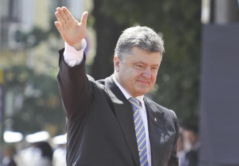 Ukraine's new president Petro Poroshenko (R) waves as he attends a flag raising ceremony after his inauguration in Kiev June 7, 2014.  REUTERS/Valentyn Ogirenko