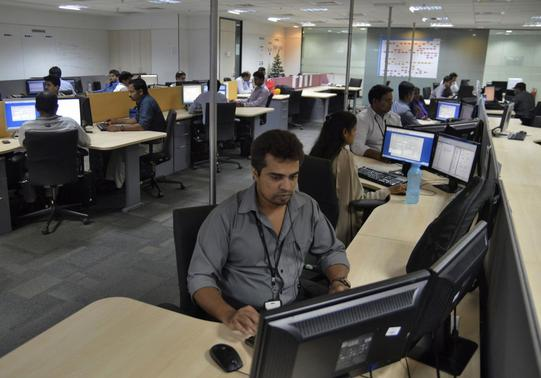 Employees of ISGN work at their stations inside the company headquarters in Bangalore June 11, 2014. REUTERS/Stringer