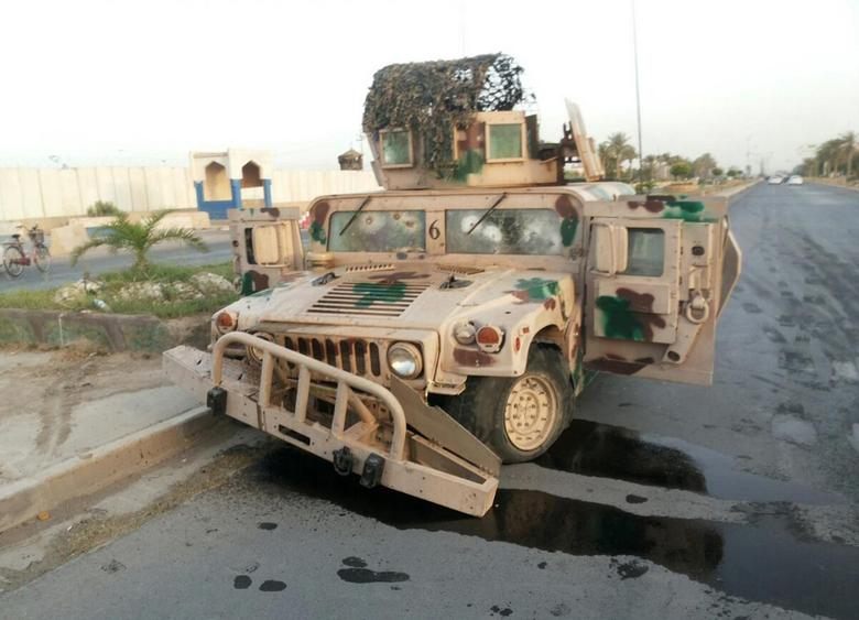 An abandoned Iraqi security forces vehicle is pictured on a road in Tikrit, which was overran by the Islamic State in Iraq and the Levant (ISIL), June 11, 2014. REUTERS/Stringer