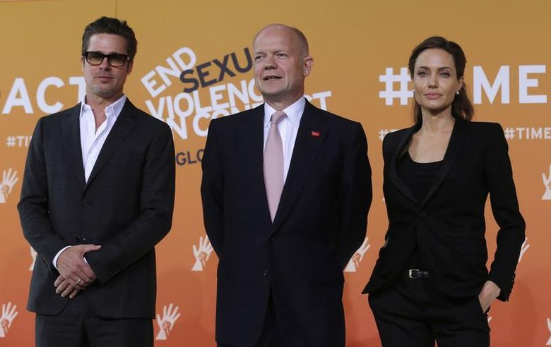 Actress and campaigner Angelina Jolie (R) poses with husband Brad Pitt (L) and Britain's Foreign Secretary William Hague as they arrive at a summit to end sexual violence in conflict, at the Excel centre in London June 12, 2014.  REUTERS/Luke MacGregor