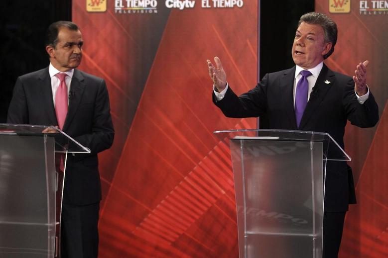 Colombia's President and presidential candidate Juan Manuel Santos (R) gestures as presidential candidate Oscar Ivan Zuluaga looks on during a television debate in Bogota June 9, 2014.  REUTERS/John Vizcaino