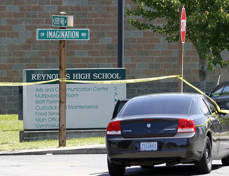 A police vehicle sits near yellow police barrier tape in front of Reynolds High School in Troutdale, Oregon June 10, 2014. REUTERS/Steve Dipaola