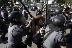 Mulher é empurrada por policiais durante protesto em São Paulo antes da abertura da Copa. 12/06/2014  REUTERS/Ricardo Moraes