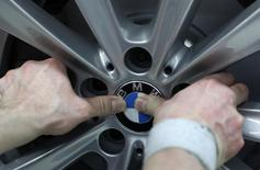 An employee places the company logo on a BMW wheel rim at the production line of the German car manufacturer's plant in the Bavarian city of Dingolfing March 6, 2012.    REUTERS/Michaela Rehle