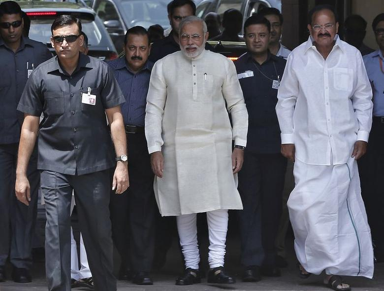 India's Prime Minister Narendra Modi (C) walks to speak with the media as he arrives to attend his first Parliament session in New Delhi June 4, 2014. REUTERS/Adnan Abidi