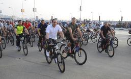 Vêtu d'une combinaison de cycliste, le président égyptien Abdel Fattah al Sissi (en blanc) a appelé vendredi ses compatriotes à faire davantage de vélo et de marche à pied pour aider le gouvernement à réduire la facture astronomique des subventions sur l'essence. /Photo prise le 13 juin 2014/REUTERS/Présidence égyptienne