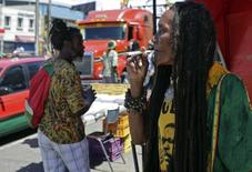 A demonstrator smokes marijuana during a march to advocate for the legalization of the plant in Jamaica, in the streets of Kingston April 20, 2014. REUTERS/Gilbert Bellamy