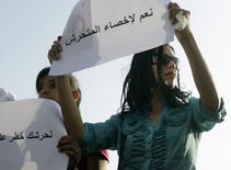 """En la imagen, una mujer sostiene un cartel que dice """"Sí a la castración de los acosadores sexuales"""" durante una protesta contra el acoso sexual, después de que una mujer fuera asaltada por una multitud en una celebración en la plaza de Tahrir, en El Cairo, el 11 de junio de 2014. Egipto pidió a YouTube que retire un vídeo que muestra a una mujer desnuda con heridas siendo arrastrada en la plaza Tahrir de El Cairo después de ser agredida sexualmente durante las celebraciones por la llegada al poder del presidente Abdel Fatah al Sisi. REUTERS/Asmaa Waguih"""