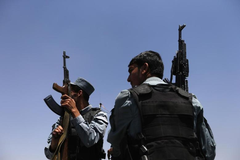 Afghan policemen keep watch as election commission workers move ballot boxes and election material to a polling station in Kabul June 13, 2014.  REUTERS/Mohammad Ismail