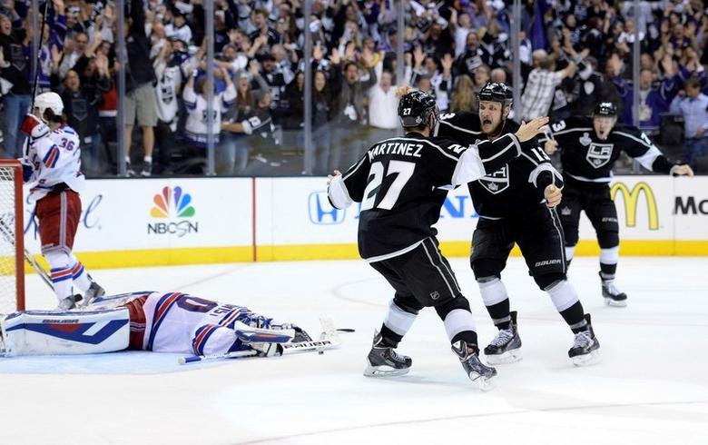 Jun 13, 2014; Los Angeles, CA, USA; Los Angeles Kings defenseman Alec Martinez (27) celebrates with teammates after scoring the game-winning goal against the New York Rangers during the second overtime period in game five of the 2014 Stanley Cup Final at Staples Center. Mandatory Credit: Gary A. Vasquez-USA TODAY Sports