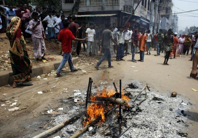 People set fire to bamboo and woods as they block a street after a clash at Mirpur area in Dhaka June 14, 2014. REUTERS/Andrew Biraj
