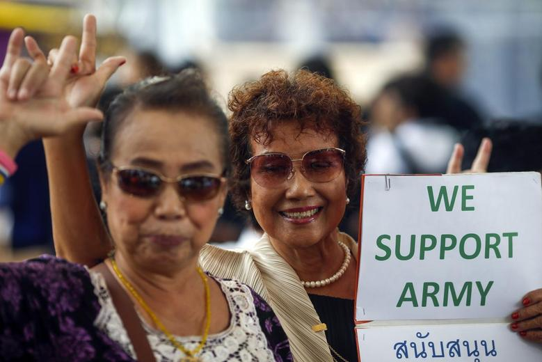 Supporters of the military gesture as they hold up a sign during a reconciliation event organized by the military at a shopping mall in Bangkok June 14, 2014. REUTERS/Athit Perawongmetha