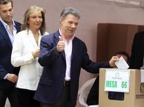 El presidente colombiano Juan Manuel Santos hace un gesto antes de dejar su voto en una urna, acompañado por su esposa María Clemencia y su hijo Martín en Bogotá, junio 15, 2014. El presidente de Colombia, Juan Manuel Santos, logró el domingo su reelección al vencer en un balotaje a su rival de derecha, una victoria que garantiza sus negociaciones de paz con la guerrilla en busca de acabar con un conflicto de medio siglo. REUTERS/Jaime Saldarriaga