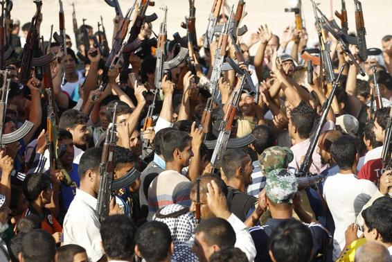 Volunteers, who have joined the Iraqi Army to fight against predominantly Sunni militants from the radical Islamic State of Iraq and the Levant (ISIL), gather with their weapons during a parade in the streets in Al-Fdhiliya district, eastern Baghdad June 15, 2014. REUTERS-Thaier Al-Sudani