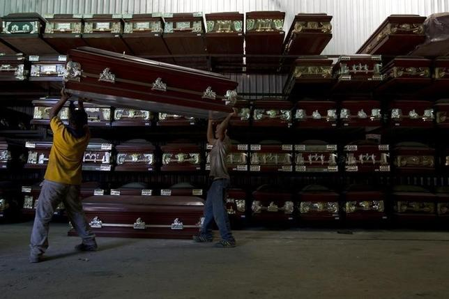 Workers carry a coffin in a caskets factory in Caracas November 29, 2012.REUTERS/Carlos Garcia Rawlins